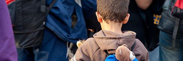 Ein kleiner Junge steht in einer Gruppe von Menschen. Er hat einen Rucksack auf, aus dem ein Teddy rausschaut.