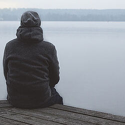 Ein Mann sitzt allein auf einem Steg am See und schaut auf das Wasser.