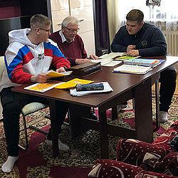 Zwei Jugendliche und ein älterer Mann sitzen an einem Tisch. Sie lernen zusammen.